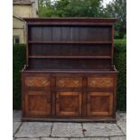 An antique oak dresser with plate rack above three frieze drawers and panel doors on plinth base.