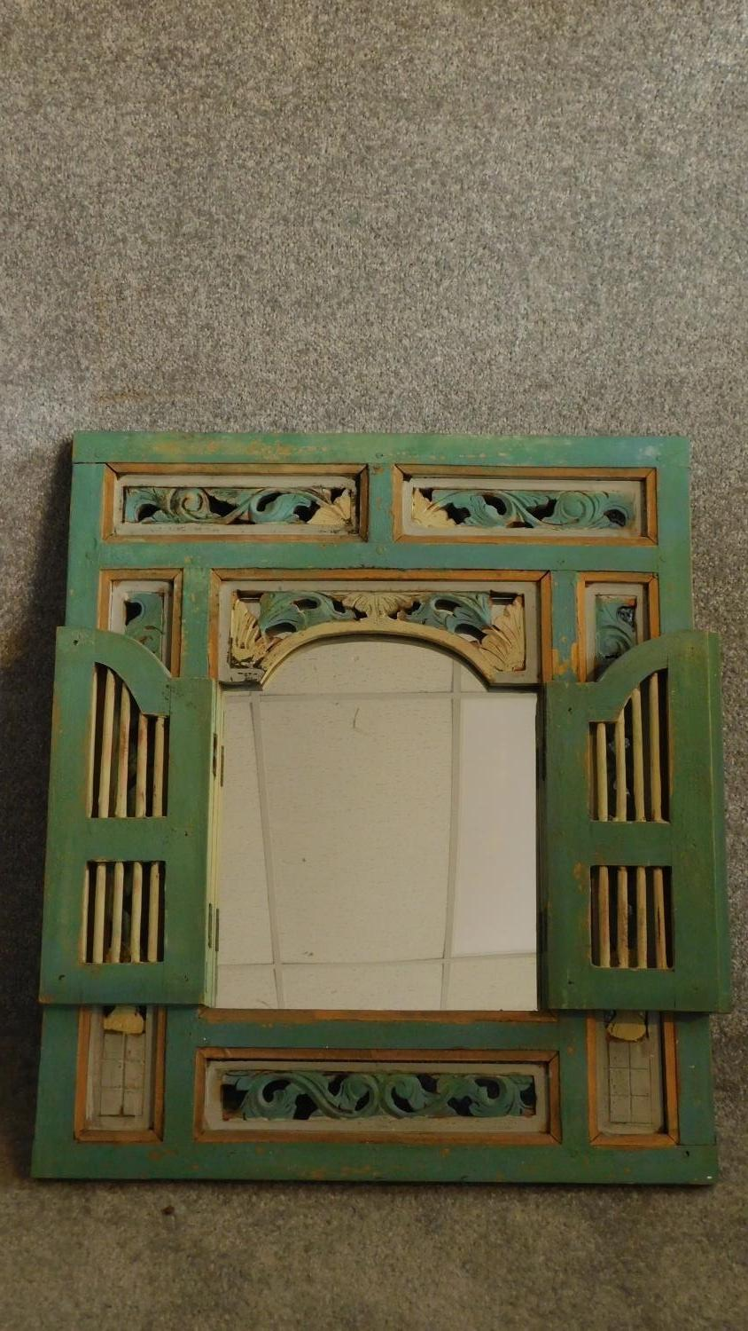 Lot 22 - A 19th Century Javanese decorative wall mounted mirror with doors and carved floral together with