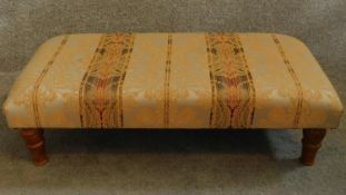 A 20th Century floral upholstered stool raised on tapering turned supports. H.26 W.91 D.46cm