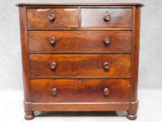 A Victorian mahogany chest of two short over three long drawers, raised on squat turned supports.