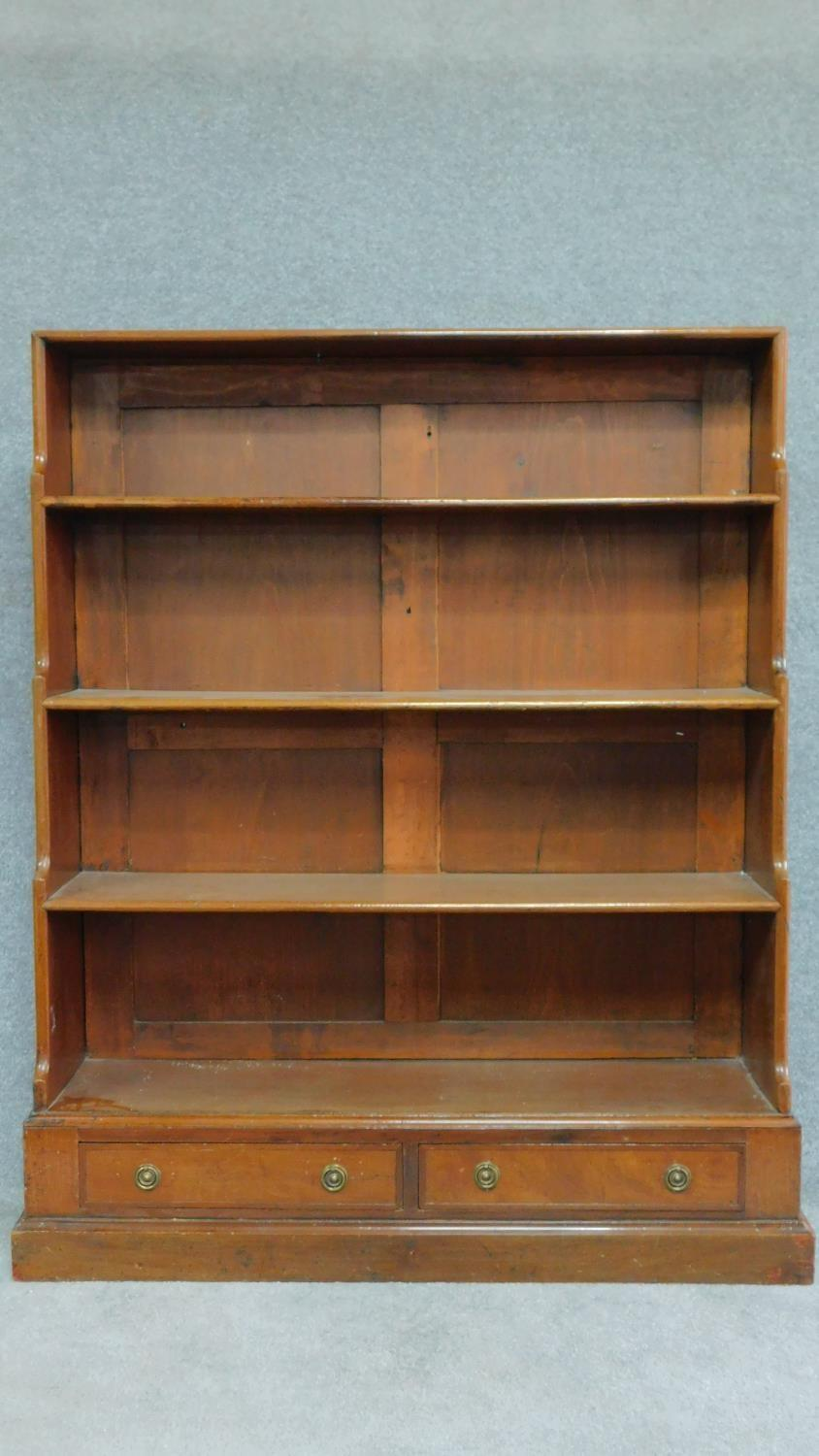 Lot 20 - A Georgian mahogany open waterfall bookshelf fitted with two base drawers. H.133 W.107 D.30cm