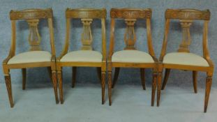 A set of four 19th century Continental walnut and satinwood inlaid chairs, lyre shaped backs on