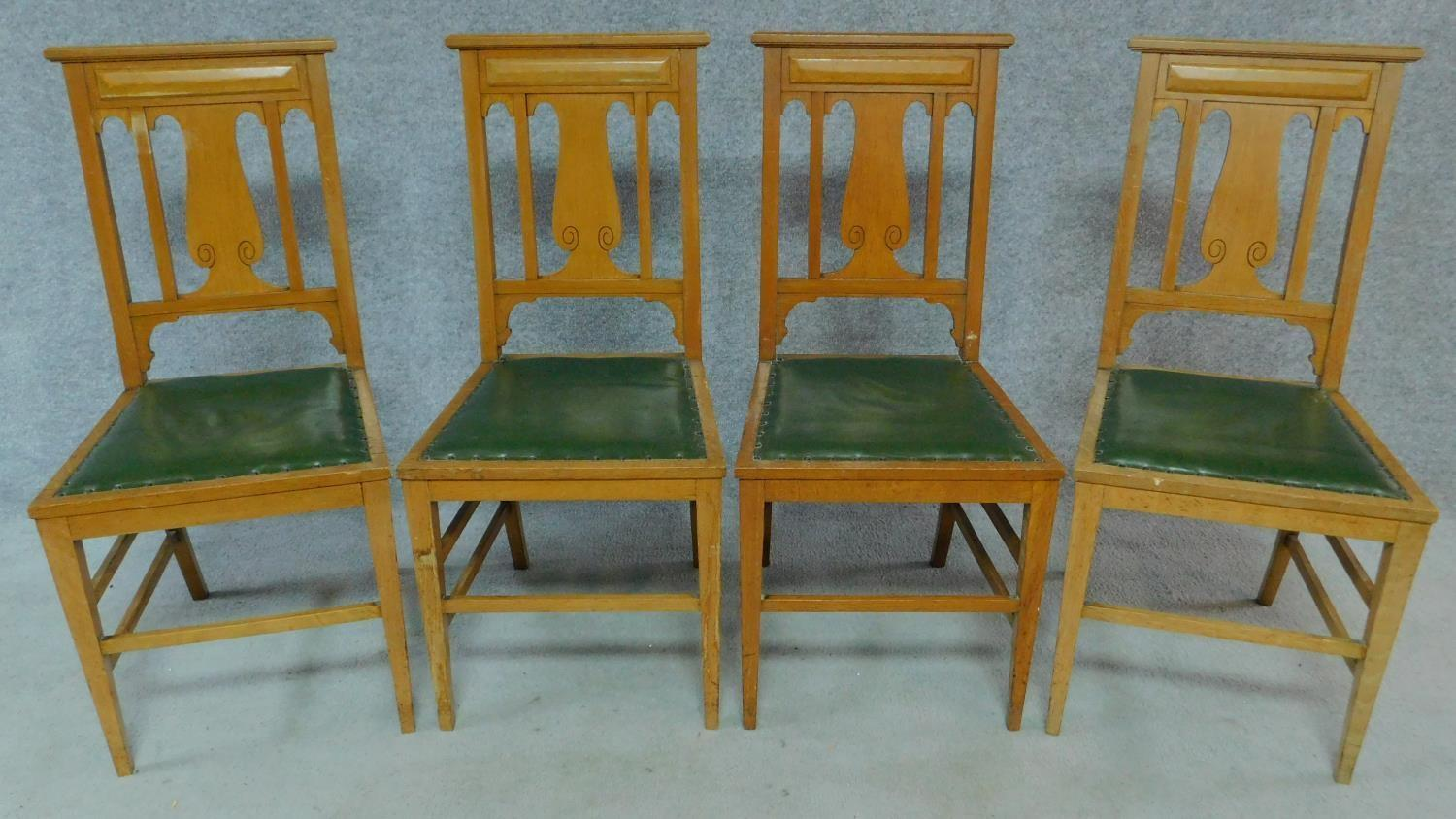 Lot 4 - A set of four Art Nouveau oak chairs with carved back and green leather upholstery raised on