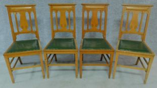 A set of four Art Nouveau oak chairs with carved back and green leather upholstery raised on