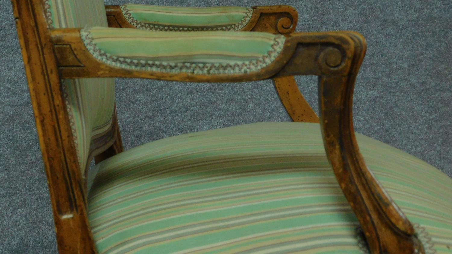 Lot 14 - A Victorian walnut armchair with floral carved details and green striped upholstery, raised on
