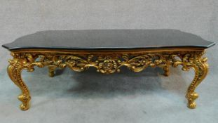 A gilt Rococo style coffee table with shaped marble top. H.47 W.139 D.79cm