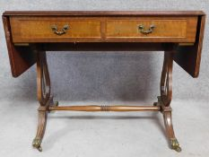 A Regency style mahogany drop flap sofa table with two dummy drawers opposing a pair of drawers.