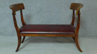 A 19th century mahogany window seat in red leather upholstery, raised on sabre supports. H.84 W.