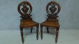A pair of Victorian oak hall chairs with carved floral shield backs, raised on tapering turned