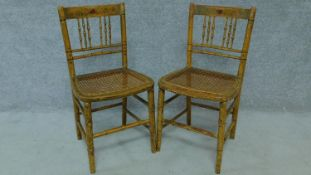A pair of 19th century faux bamboo cane seated chairs with hand painted floral design and raised