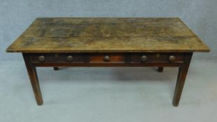 A 19th century oak refectory dining table with three frieze drawers raised on square tapering