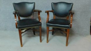 A pair of beech framed office chairs in black faux leather upholstery. H.84cm