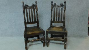 A near pair of antique country oak chairs raised on stretchered turned supports. H.103cm