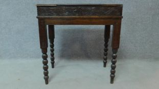 A late 19th Century oak writing desk with floral carving and bobbin turned supports. H.70 W.66 D.