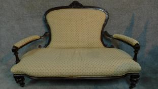 A Victorian carved mahogany framed open arm two seater sofa on turned tapering supports. H.104 W.