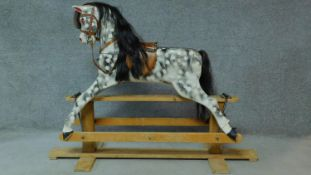 A vintage carved piebald rocking horse with lift off top section. H.115 W.156cm