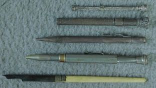 A collection of five antique writing implements. Including two white metal propelling pencils with