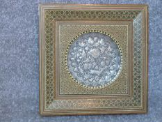 A framed Persian Khatam horn and wood marquetry framed silver and copper repousse plaque with