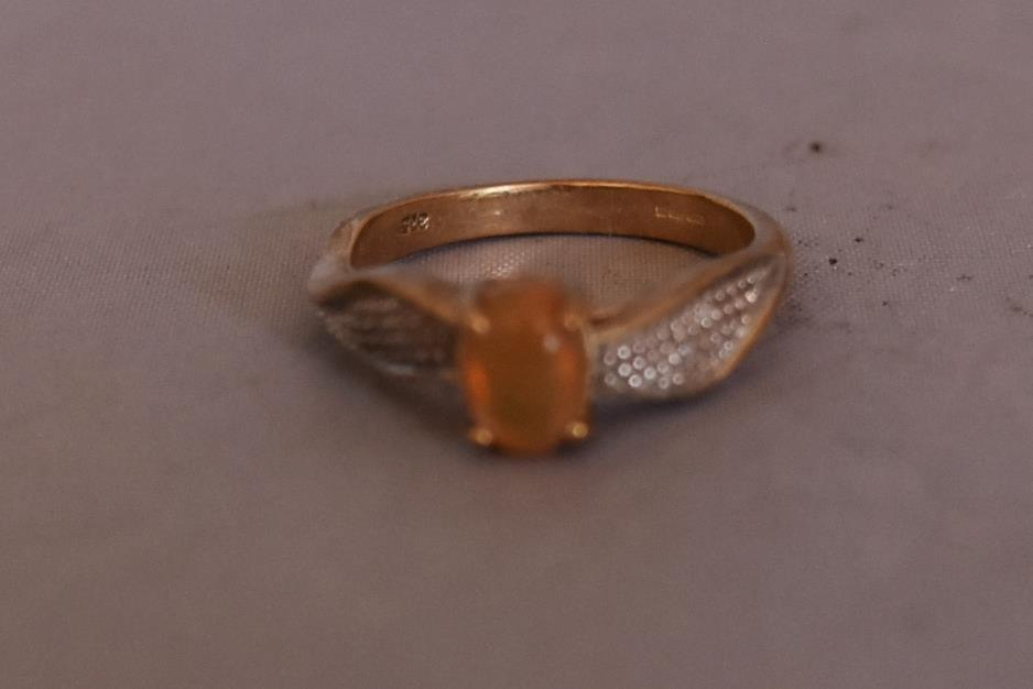 A modern Kalimaya opal and diamond flanked solitaire ring. Set to centre with an oval cabochon