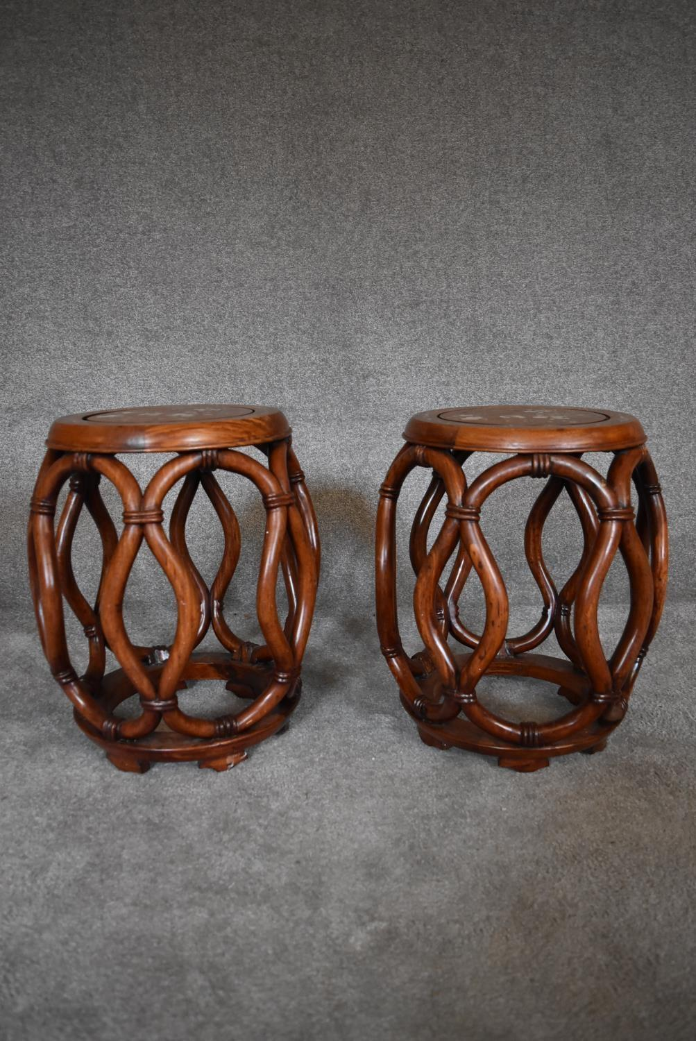 A pair of Chinese rosewood and mother of pearl inlaid barrel shaped stools with latticework sides.
