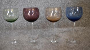 A set of four crystal coloured wine glasses. H.23cm