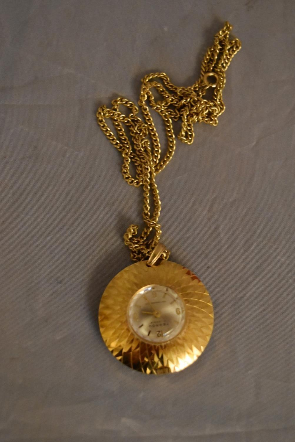 A vintage Tegrov gold tone pendant antimagnetic watch and chain. Impressed floral design to the back