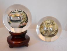 A pair of reverse painted glass spheres, one mounted on a wooden stand, one depicting a landscape