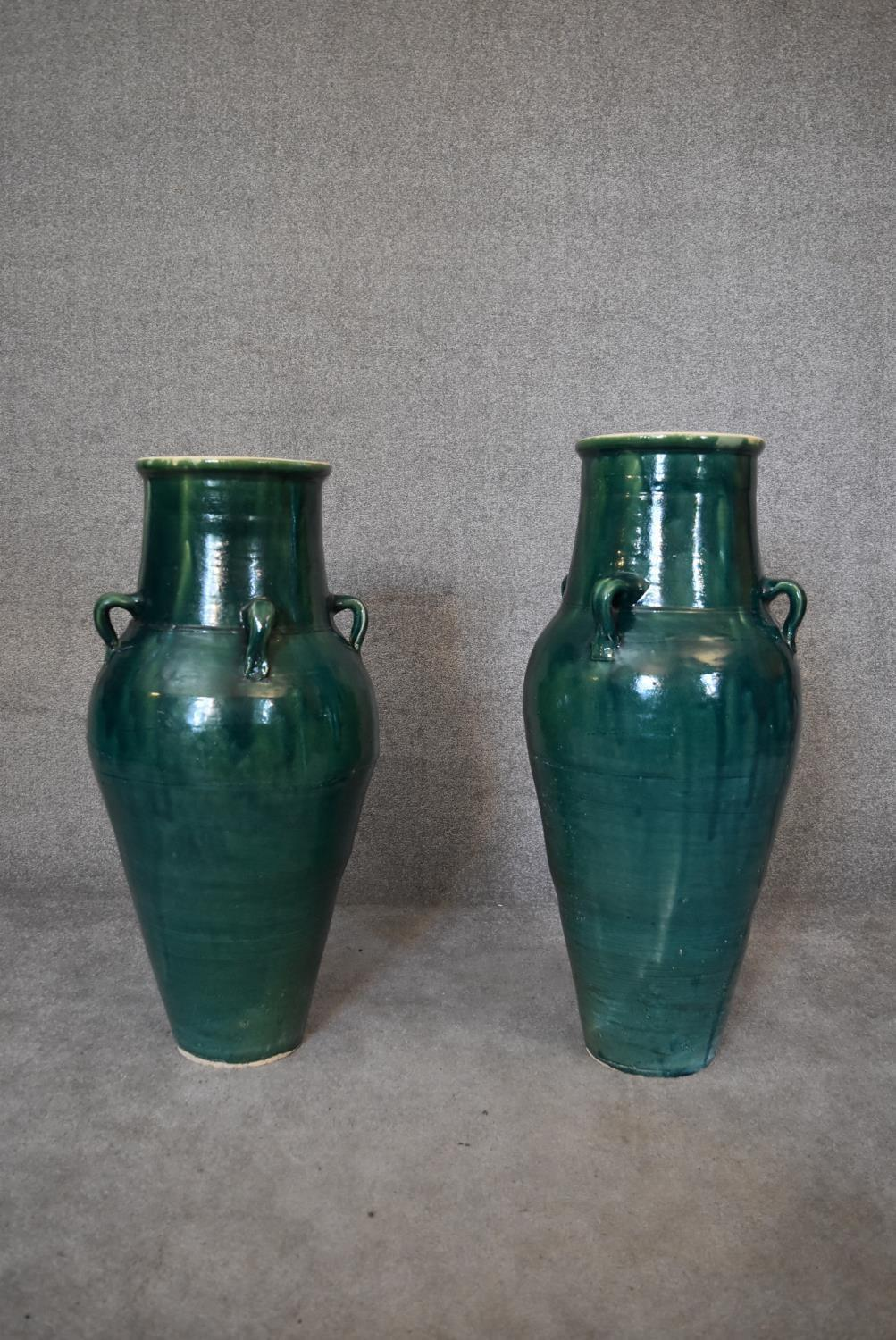 A pair of large green glazed sharab wine vessels. H.90 x 26cm