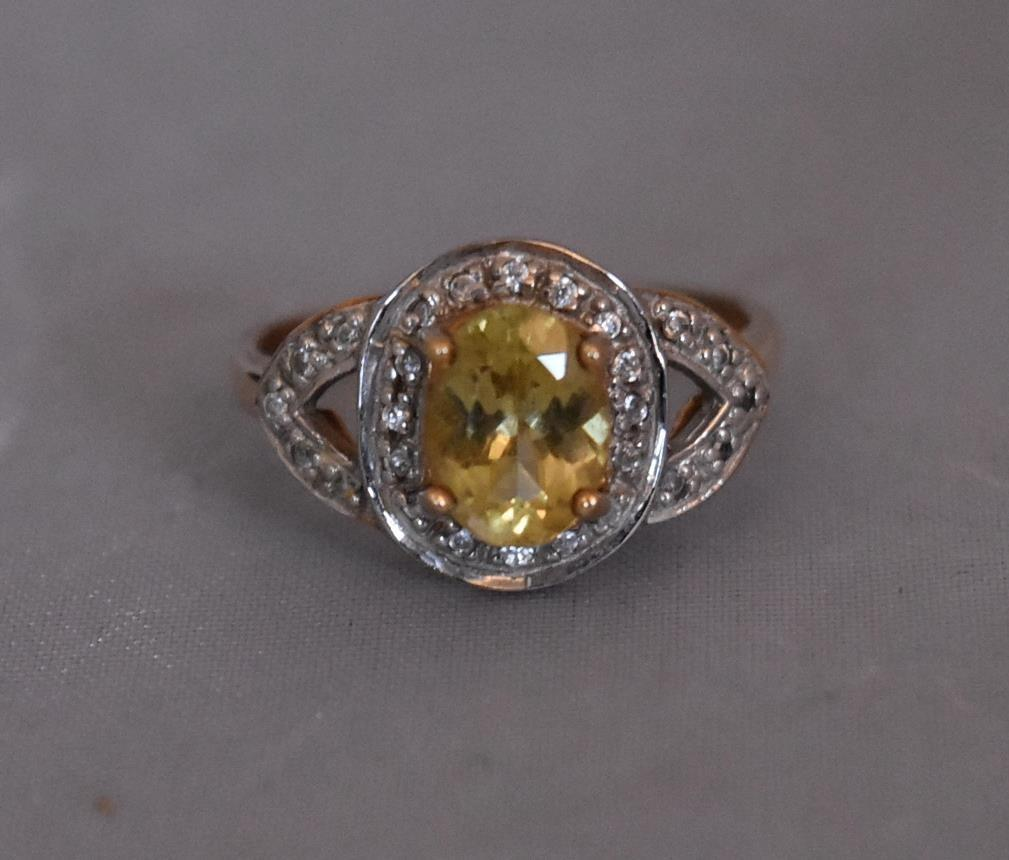 A modern Lemon apatite and zircon cluster ring. Set to centre with an oval mixed cut Lemon Apatite