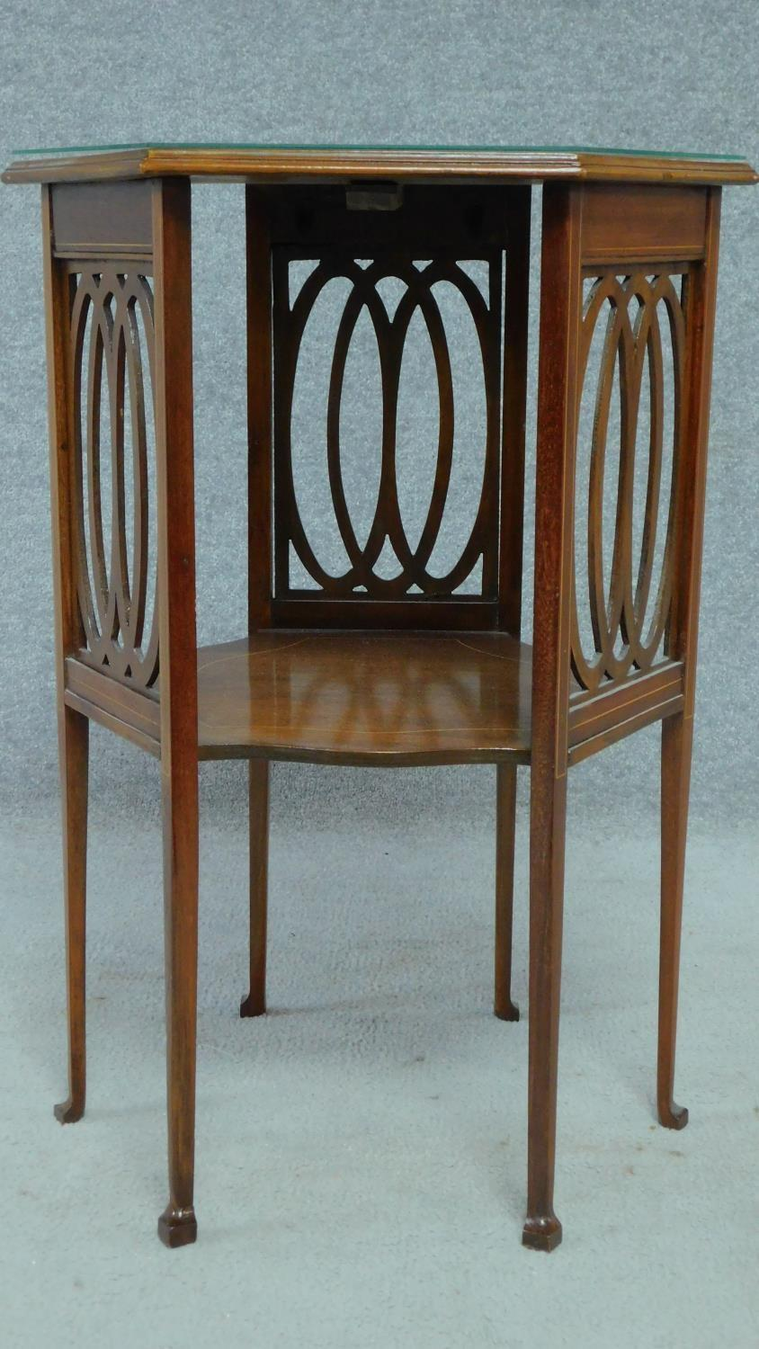 An Arts & Crafts mahogany and satinwood inlaid hexagonal carved lamp table raised on square tapering