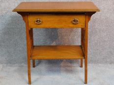 An Arts and Crafts oak hall table with frieze drawer and under tier, raised on square supports. H.75