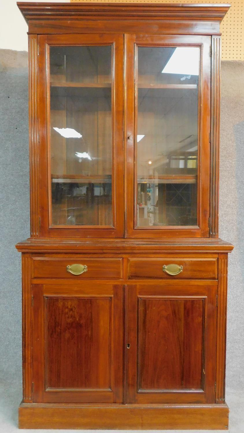 A late 19th century walnut library bookcase with glazed upper section above pair of frieze drawers