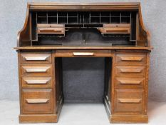 A late 19th century oak roll top desk with tambour shutter enclosing fitted interior above an