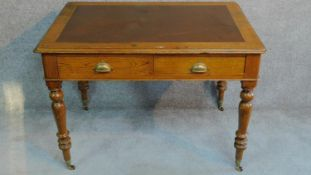 A Victorian oak leather inset two drawer writing table with frieze drawers raised on turned tapering
