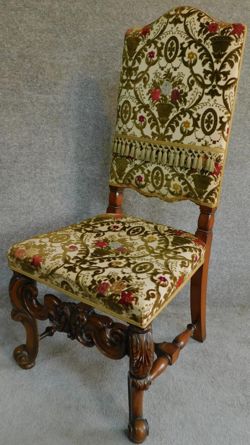 A Victorian carved oak armchair with tapestry style floral upholstery, raised on stretchered