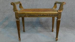 A Victorian gilt stool with caned seat on square tapering supports. H.59 W.69 D.36cm