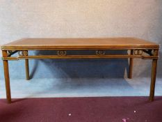 A Chinese hardwood rattan topped dining table raised on circular section supports. Possibly retailed
