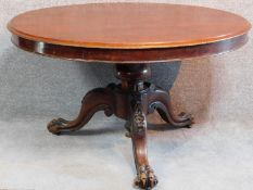 An early Victorian mahogany circular tilt top loo table raised on carved tripod base with lion paw