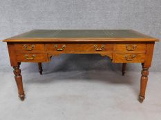 A Victorian walnut writing table with leather insert top and long central frieze drawer and four