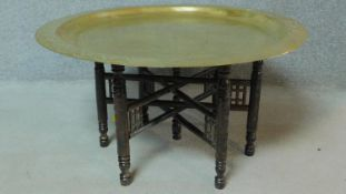 An Eastern decorative brass centre table with carved base. H.45 W.89 D.89cm
