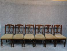 A set of six late Victorian carved walnut dining chairs raised on turned tapering supports. H.91cm