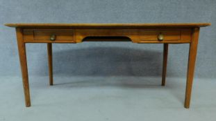 A mid 20th century teak writing table fitted inset tooled pale green leather top with two frieze