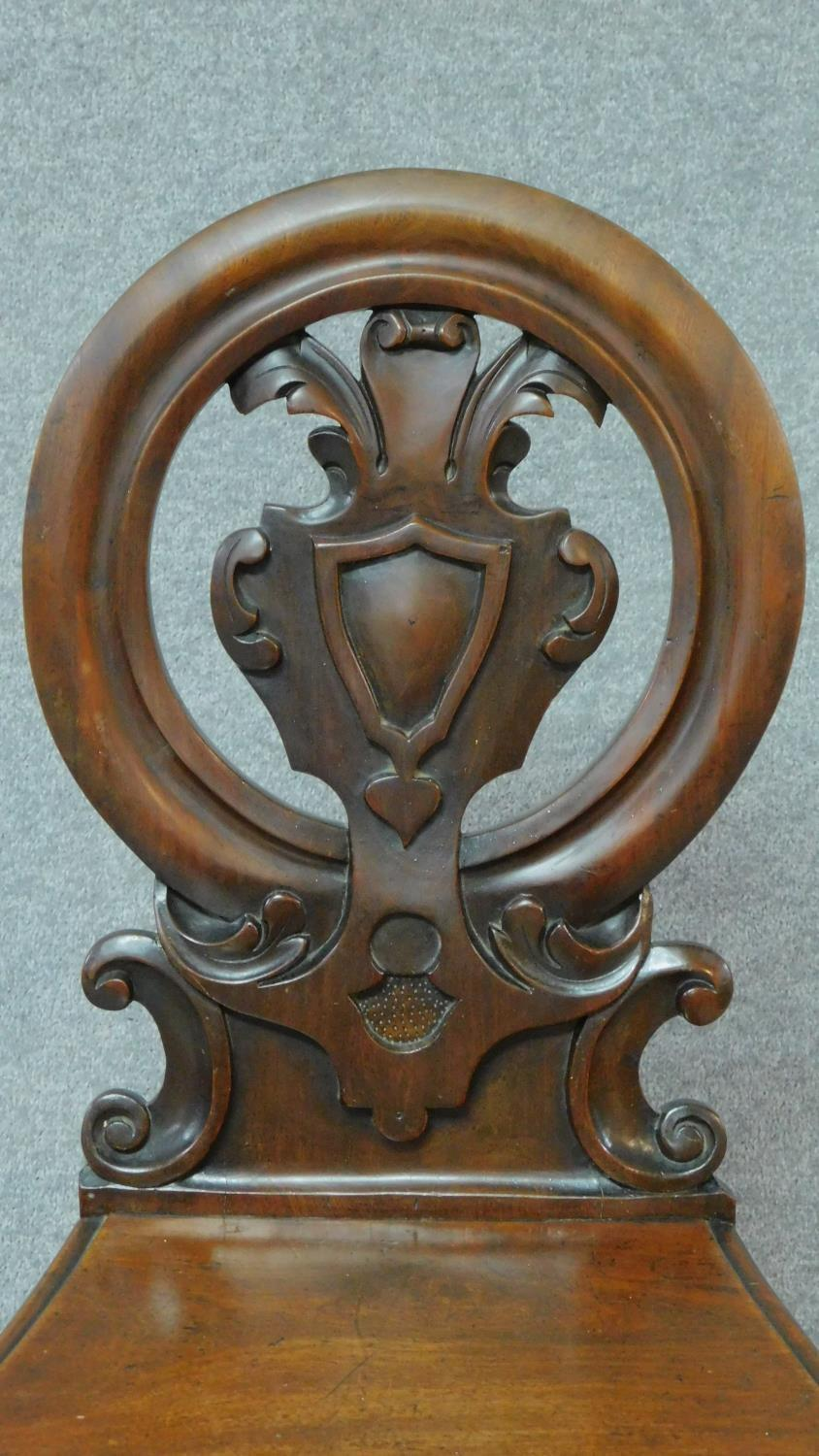 A pair of Victorian oak hall chairs with carved floral shield backs, raised on tapering turned - Image 3 of 7