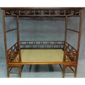 A Chinese hardwood four poster bedframe with woven base and pierced fretwork canopy. H.201 W.280 D.