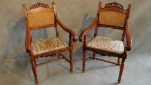 A pair of Italian fruitwood carved armchairs in floral upholstery raised on turned stretchered