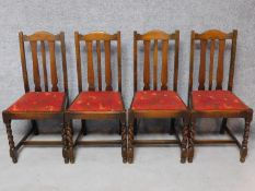 A set of four antique style carved oak dining chairs on stretchered barleytwist supports. H.95cm