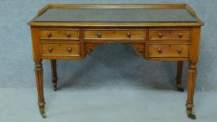 A William IV mahogany writing table with glass inset top and five frieze drawers, raised on tapering
