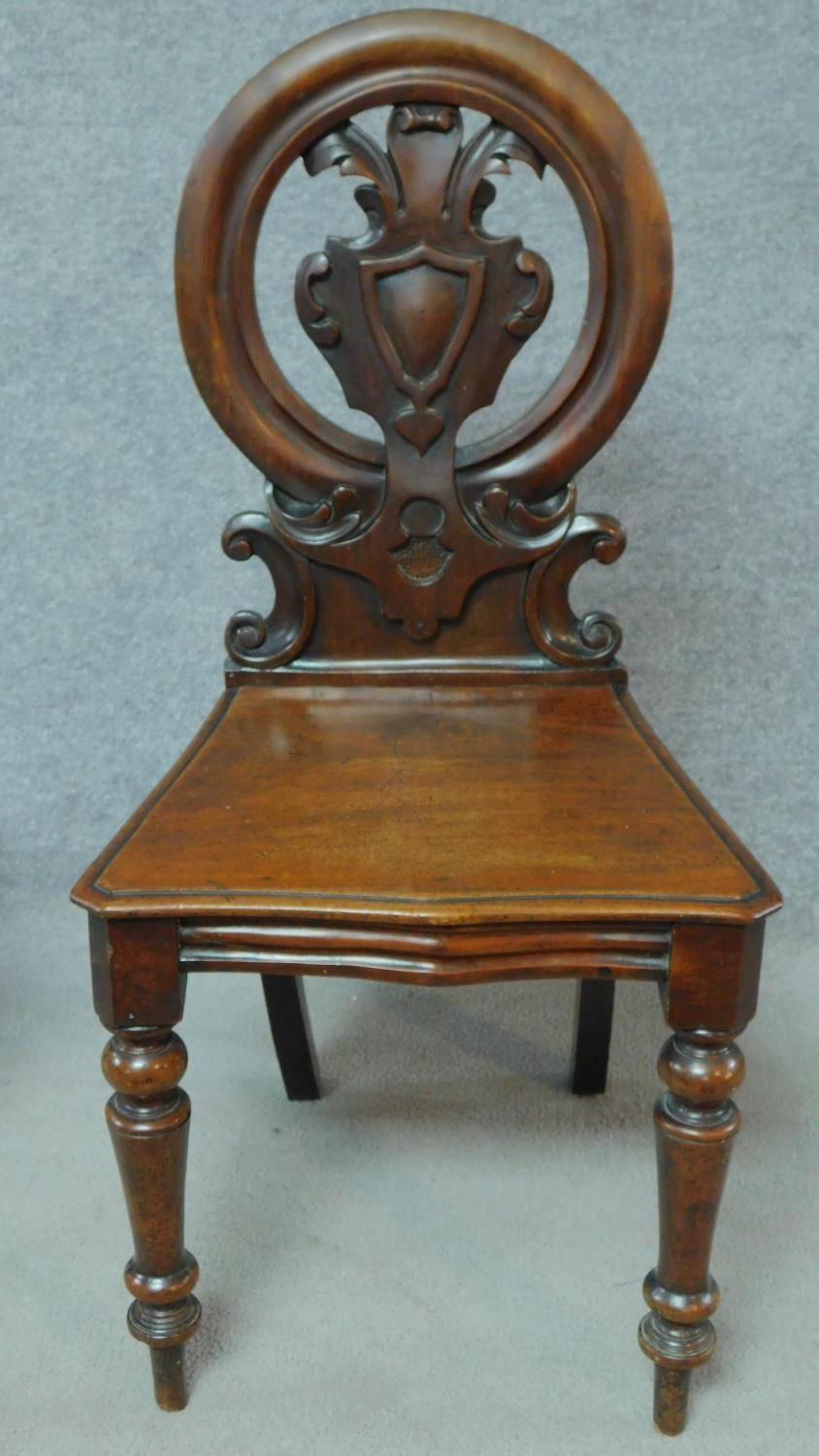 A pair of Victorian oak hall chairs with carved floral shield backs, raised on tapering turned - Image 2 of 7