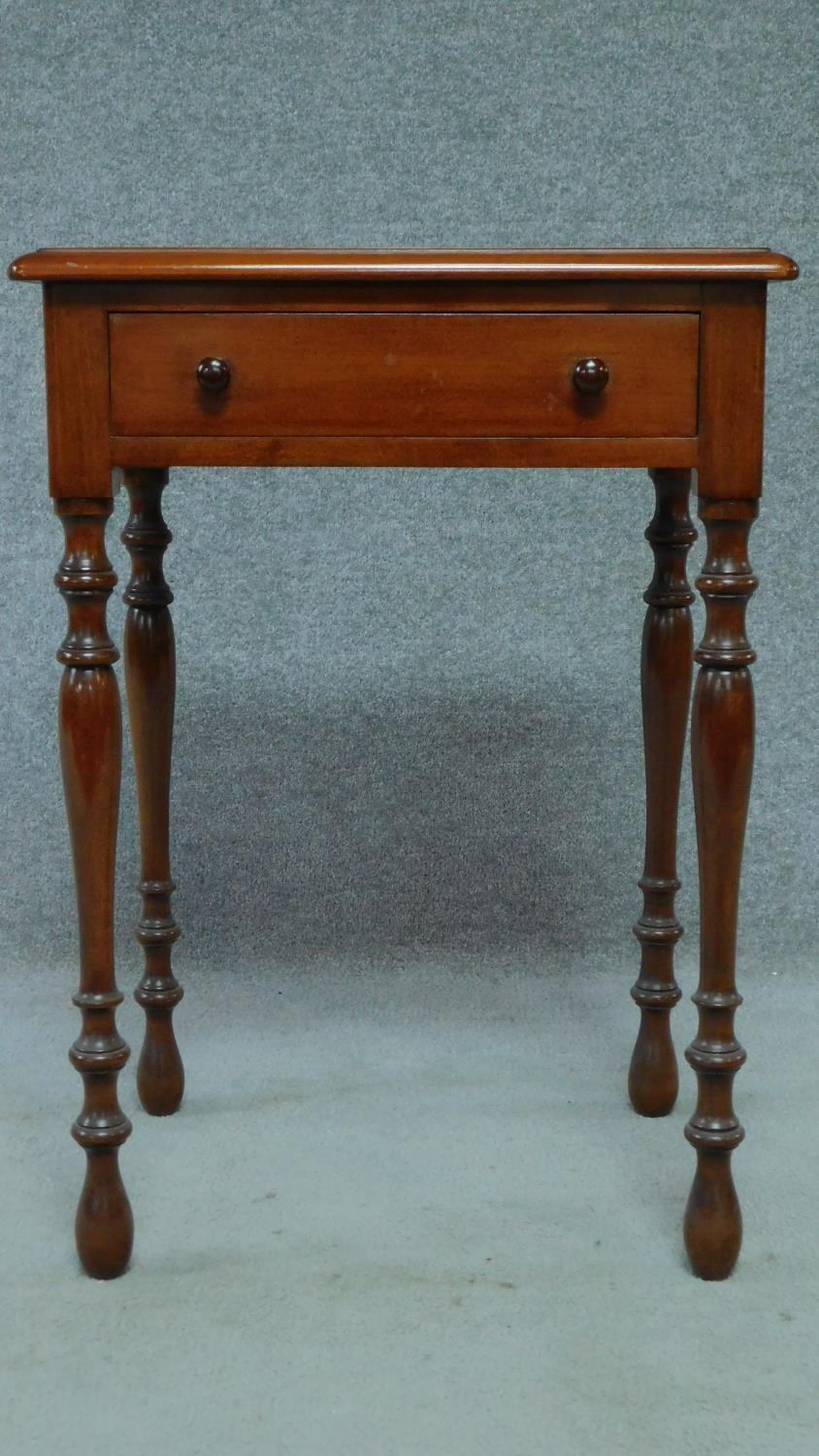 A late 19th century mahogany bedside table with frieze drawer, raised on turned tapering supports.
