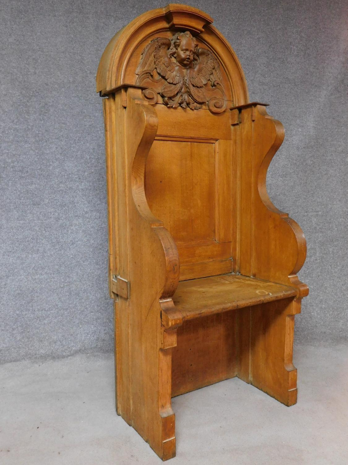 A 19th century oak hall bench with cherub carved mask above panel back on solid seat. H.169 W.75 D. - Image 2 of 7